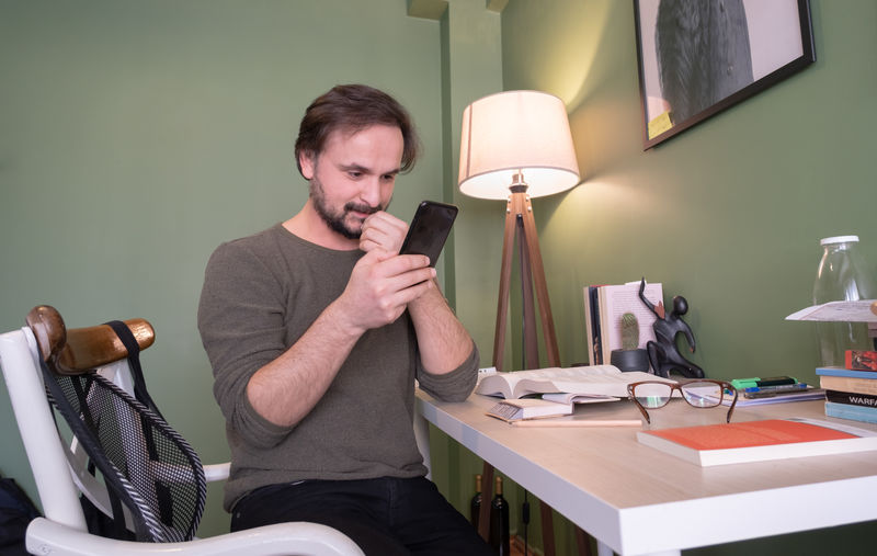 Man using mobile phone while sitting at home