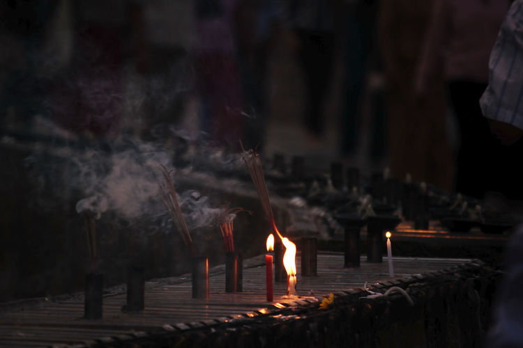 Lit candles in temple against building