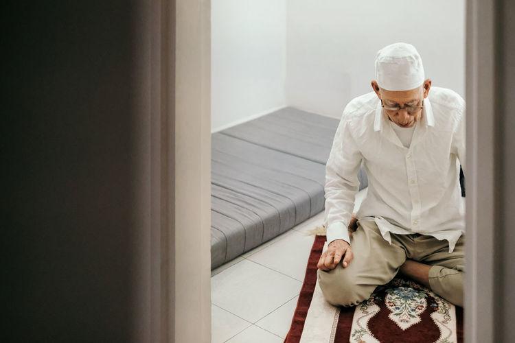Senior man praying at home seen through doorway