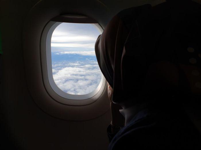 Woman looking through airplane window