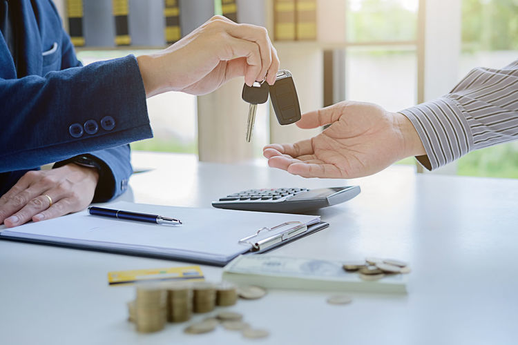 Cropped hand of businessman giving car keys to man on table