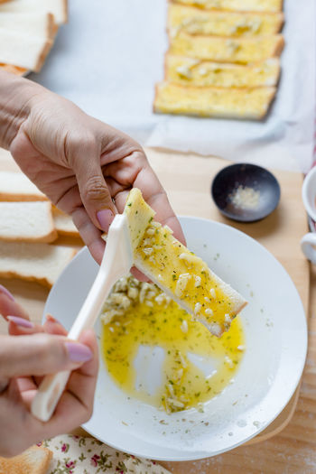 Homemade Brush Butter Close-up Day Food Food And Drink Freshness Garlic Bread Healthy Eating Holding Human Body Part Human Hand Indoors  Lifestyles One Person Plate Ready-to-eat Real People Women