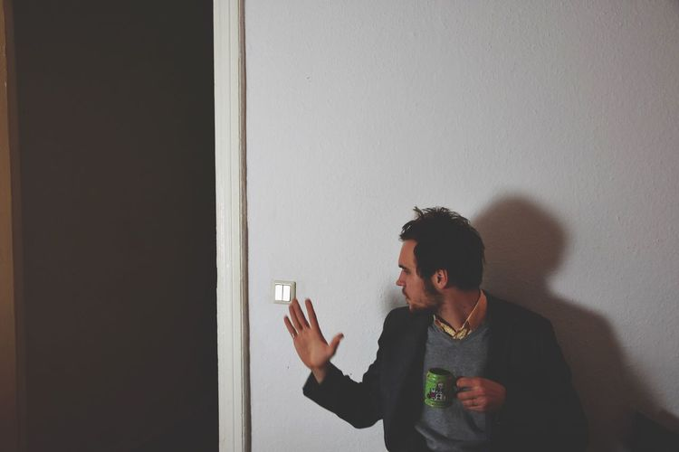 Man gesturing while holding tea cup against wall at home