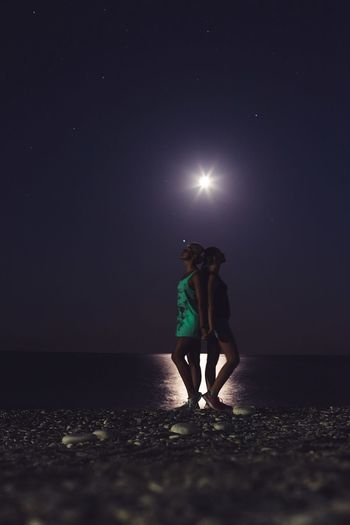 Side view of women standing at beach against sky during night