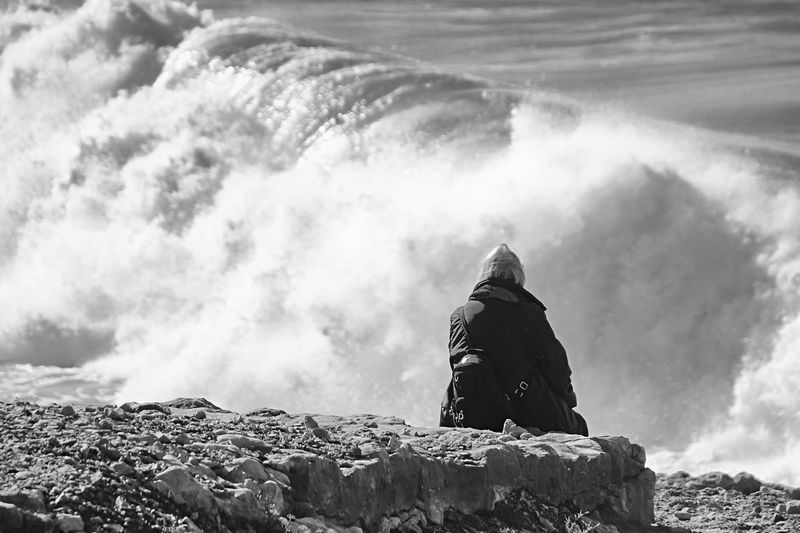 Rear View Of Person Sitting On Rock In Front Of Wave At Sea Shore