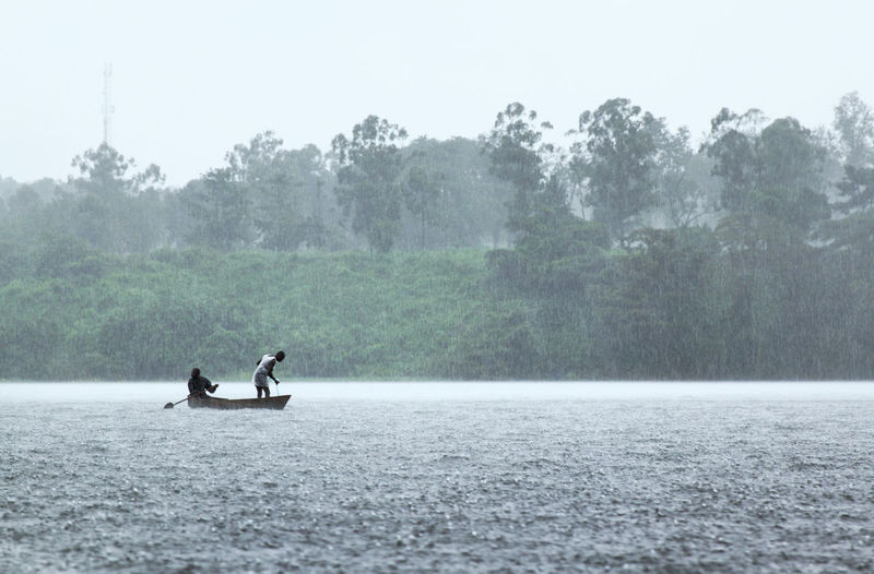 Men sailing on rowboat in river during rain