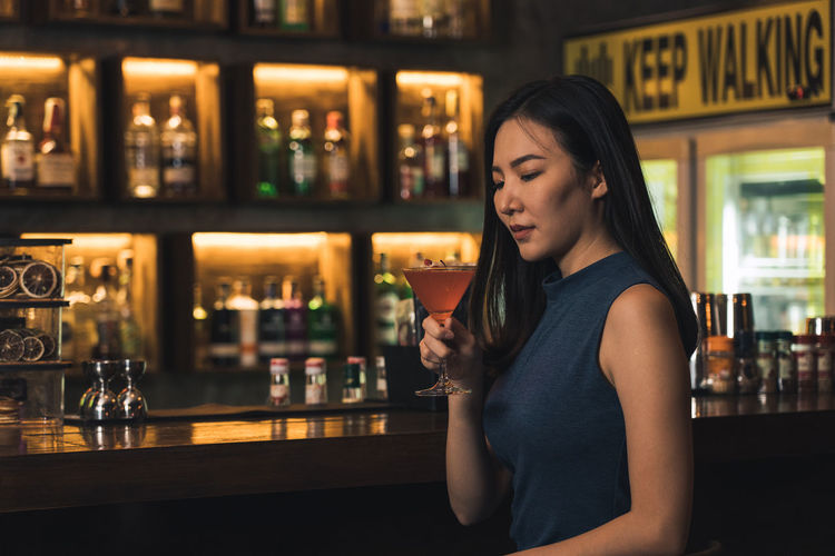Young woman drinking glass on table at bar