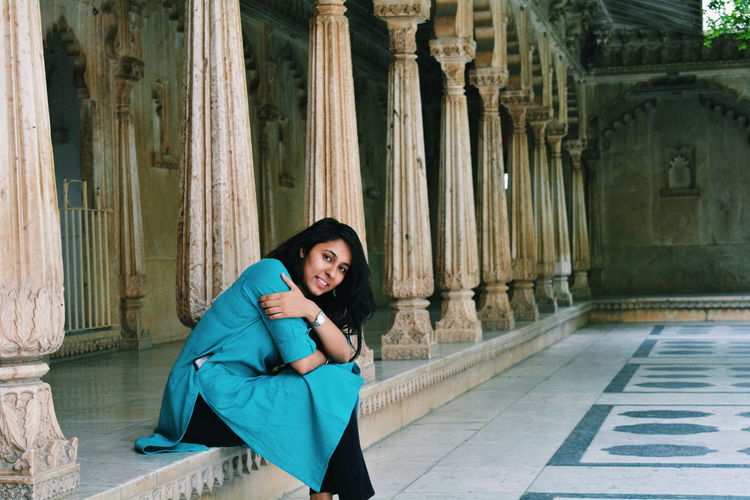 Portrait of smiling young woman sitting at historic building