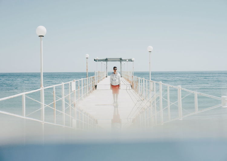 Surface Level View Of Man Standing On Pier In Sea