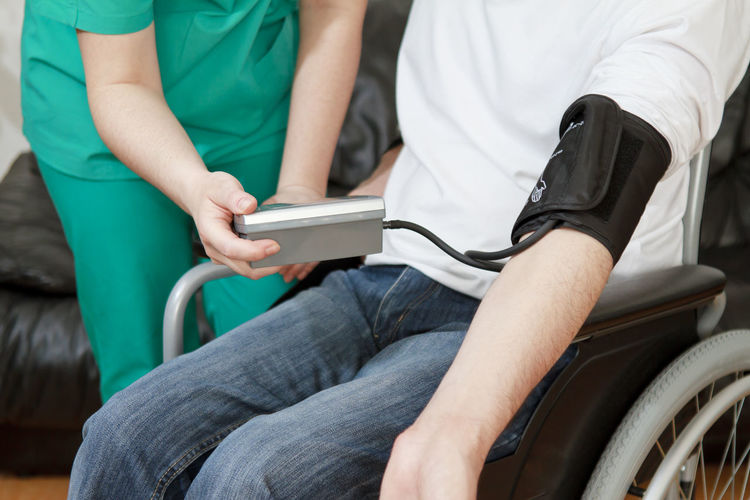 Midsection of nurse examining patient on wheelchair in hospital