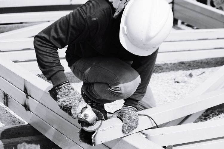 Construction worker cutting metal at site