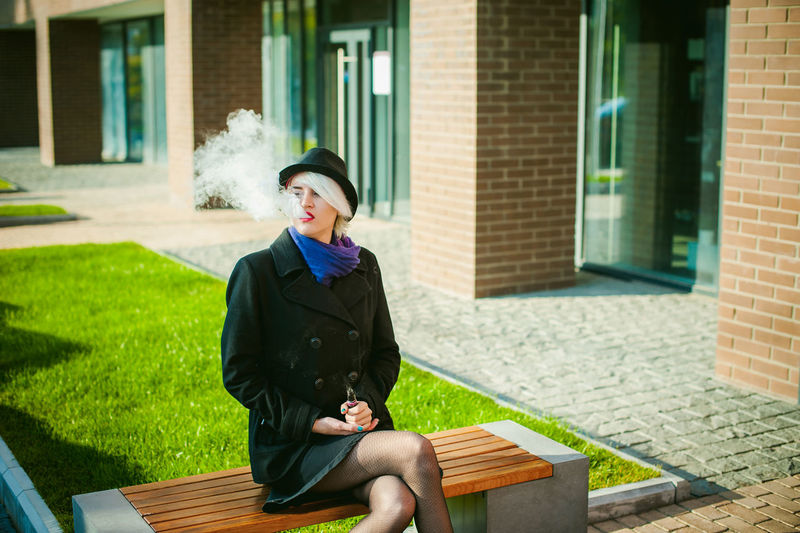 Young Woman Smoking While Sitting On Bench At Park