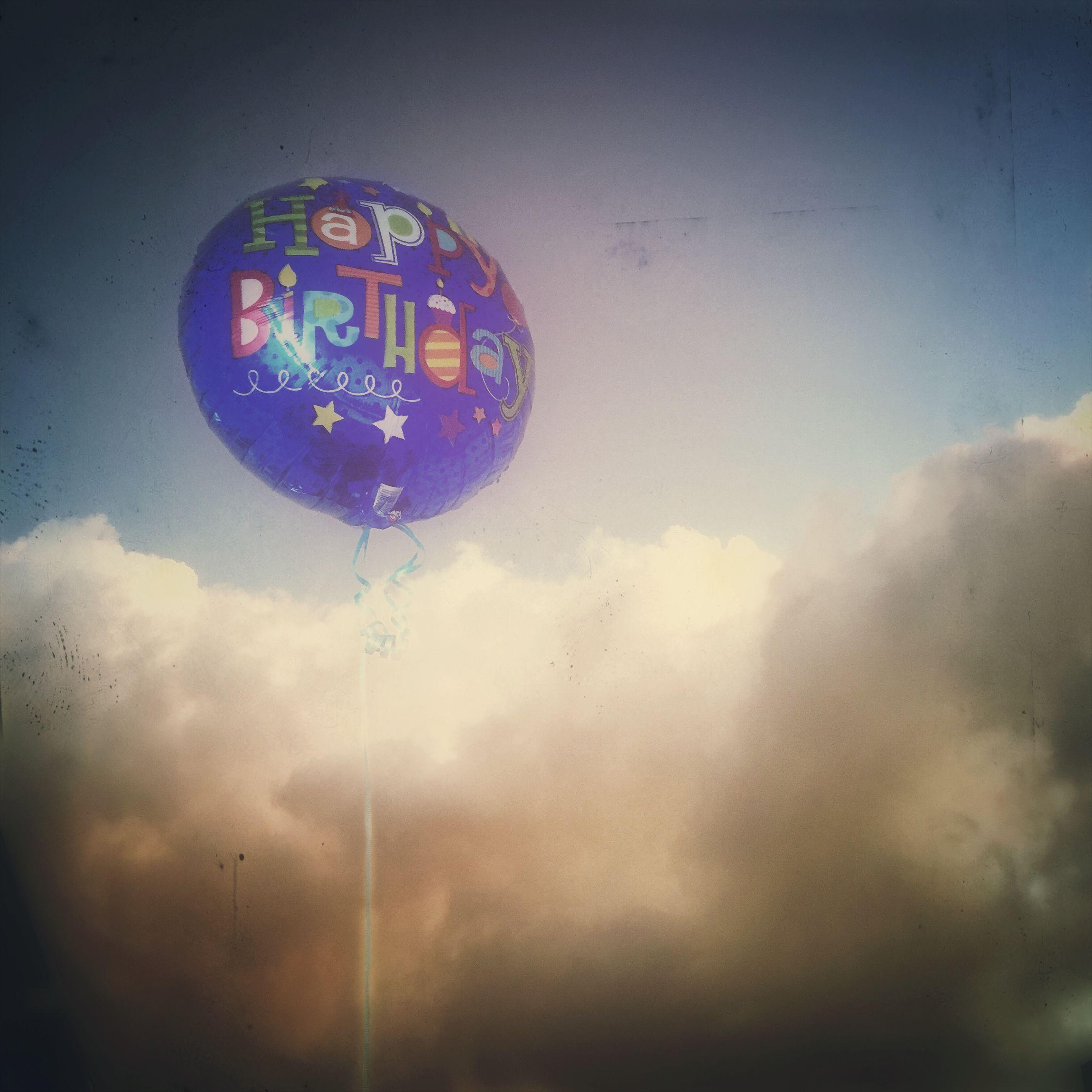 sky, low angle view, illuminated, lighting equipment, mid-air, sphere, cloud - sky, multi colored, street light, ferris wheel, dusk, blue, outdoors, flying, transportation, no people, amusement park, circle, amusement park ride, night