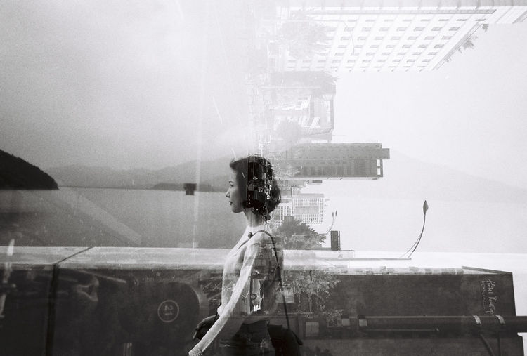 Double Exposure Of Young Woman And Buildings