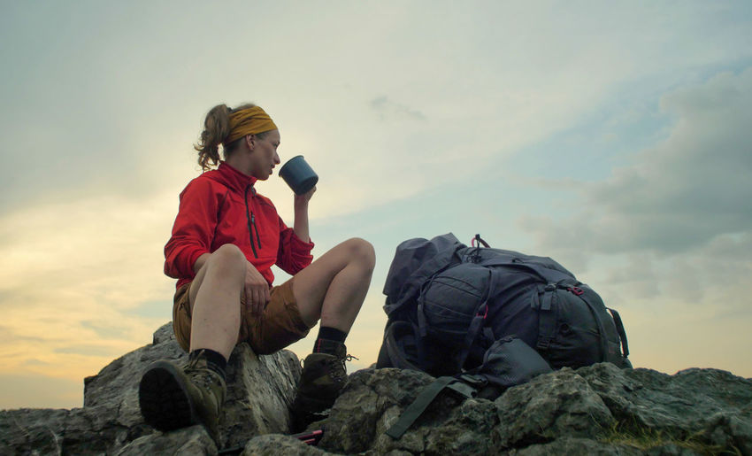 caucasian female hiker sitting on a rocky peak next to a backpack drinking beverage out of a mug Alpine Backpacking Boots Camping Expedition Freedom Hiking Nature Sitting Travel Trekking Woman Active Activity Adventure Backpack Casual Clothing Childhood Cloud - Sky Female Full Length Hiking Hobby Leisure Activity Lifestyles Mountain Nature One Person Outdoors Peak People person Real People Rock Rock - Object Sitting Sky Solid Trek