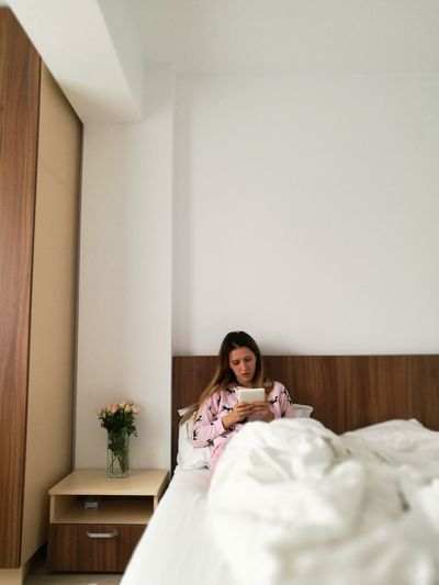 Woman on bed using digital tablet at home
