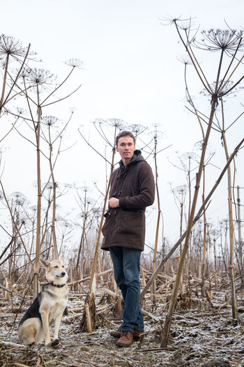 Full length of man standing with dog in forest