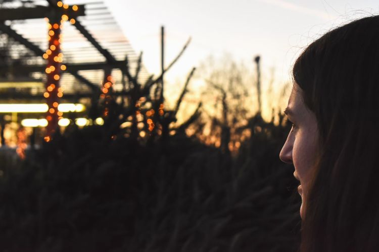 Side View Of Young Woman Looking Away At Sunset