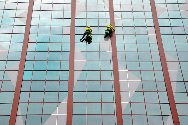 Low angle view of men working on a skyscraper