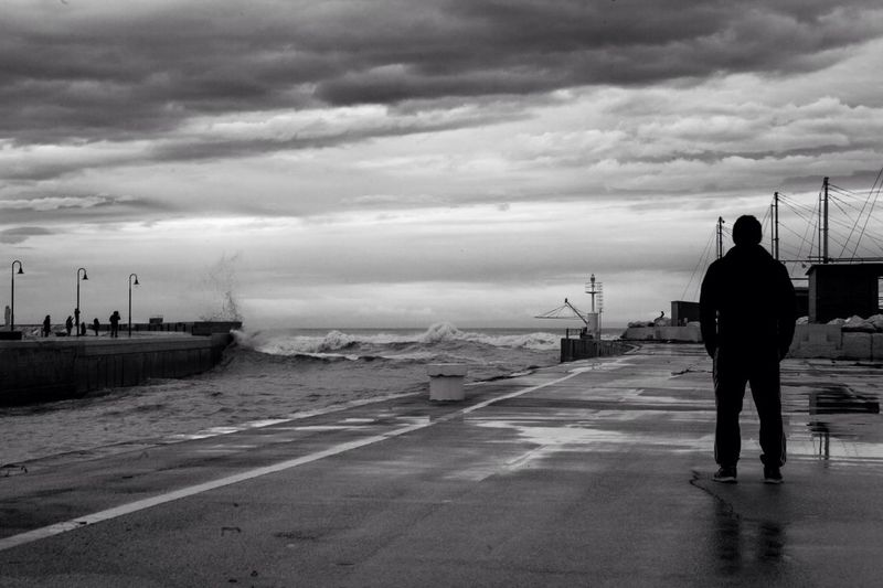 Full Length Rear View Of Man Standing By Sea At Dusk