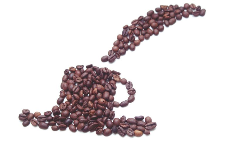 Close-up of coffee beans on table against white background