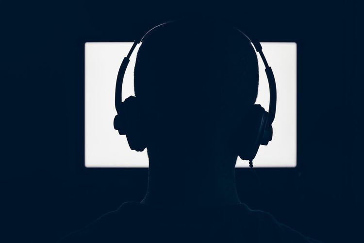 Man in headphones sits in front of a blank monitor in dark room Silhouette One Person One Man Only Headshot Backlight Behing Black Background Bright Concept Desktop Desktop Pc Obscured Face Unrecognizable Person Headphones Mockup Technology Game Videogames Gaming PC Sitting Sitting Alone Tv Television Watching Widescreen White Color Listening Screen Man Rear View Human Head Adult