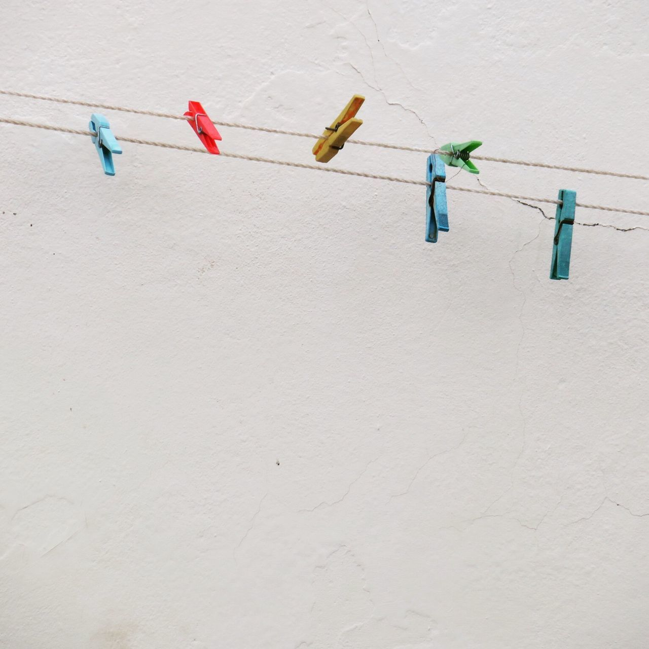 Low Angle View Of Clothespins On Rope Against Wall