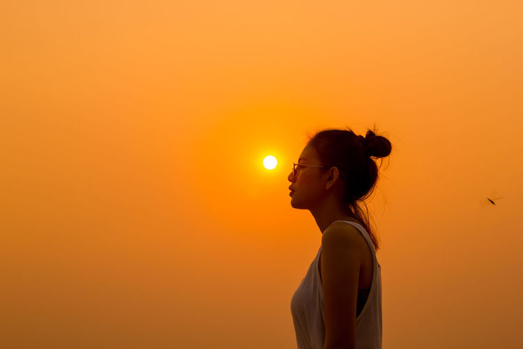 Young woman standing against clear orange sky