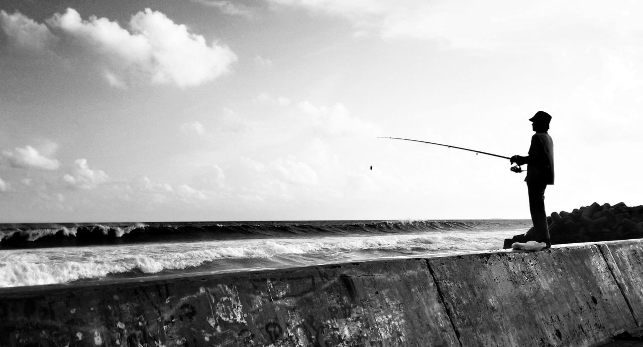 Man fishing while standing on wall