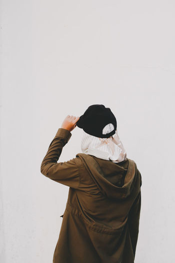 Midsection of person wearing hat standing against white background