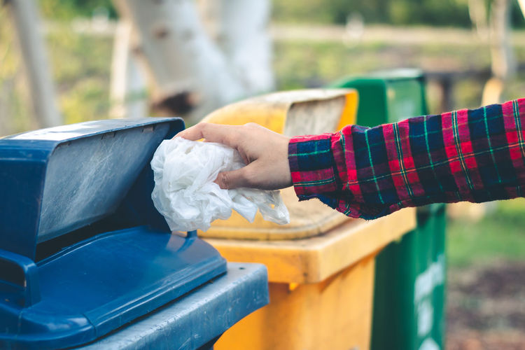 Cropped hand of person throwing garbage in bin