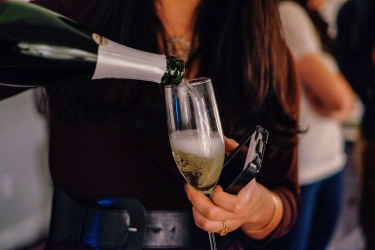 Midsection Of Woman Pouring Champagne In Glass
