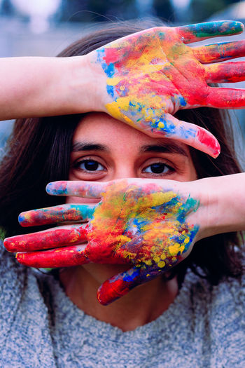 Close-up portrait of woman showing colorful powder paint on hands