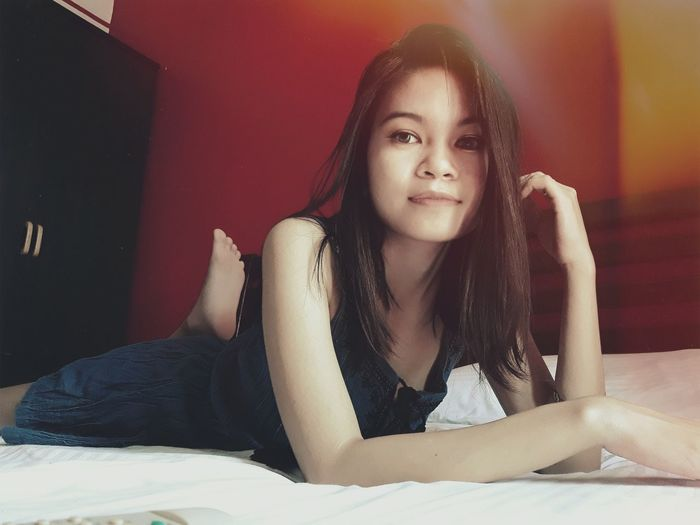 Portrait of beautiful young woman lying on bed at home