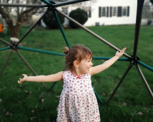 Cheerful girl standing against play equipment at park