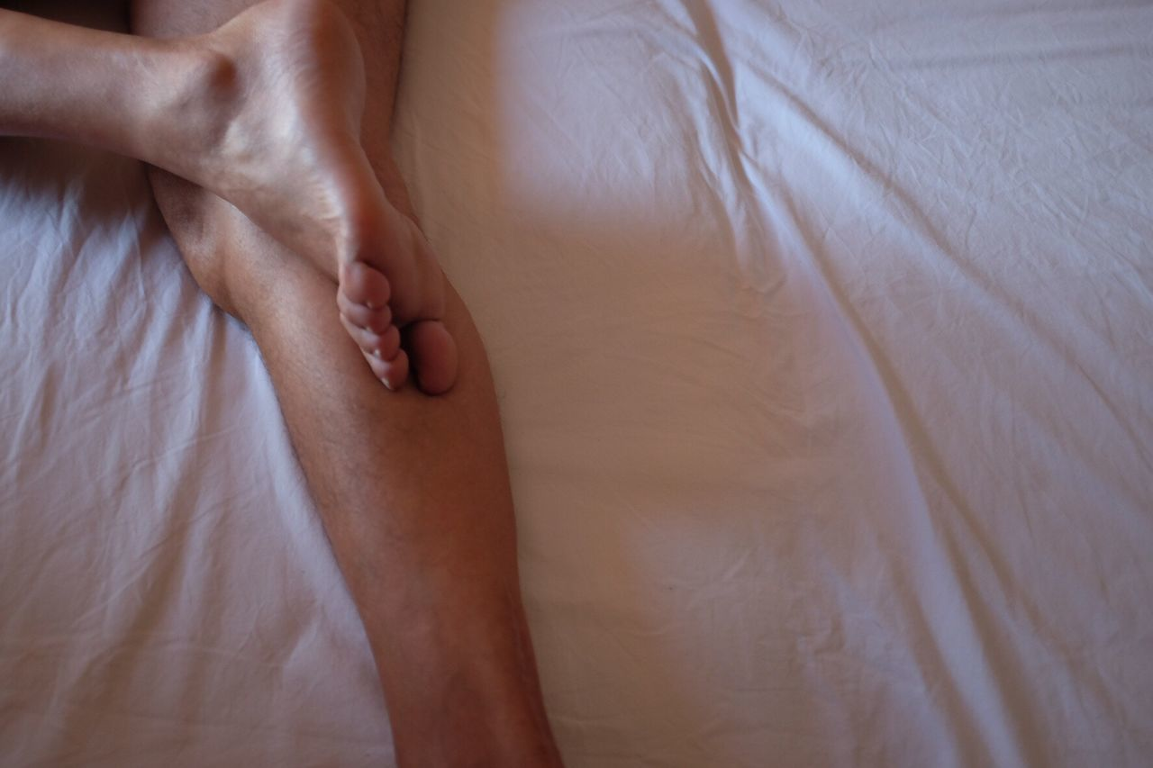 human skin, indoors, human body part, human leg, bed, low section, togetherness, barefoot, relaxation, men, close-up, real people, women, bedroom, two people, human hand, bonding, day, adult, people