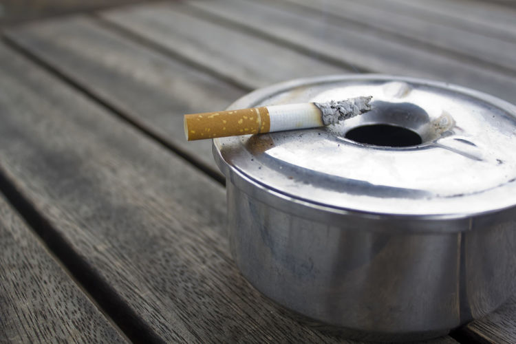 Cigarette and Ashtray on a wood table Burning Copy Space Lifestyle Addiction Ash Ashtray  Ashtray  Bad Habit Cigar Cigarette  Cigarette  Cigarette Butt Container Habit Illness Metal Nicotine No People RISK Smoking Issues Social Issues Tabacco  Toxic Unhealthy Wood - Material