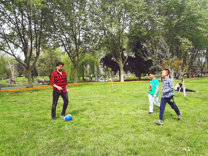 Full length of man playing soccer with boys at park
