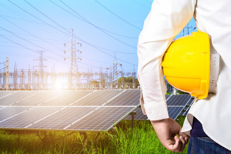Midsection of engineer with hardhat standing against solar panel