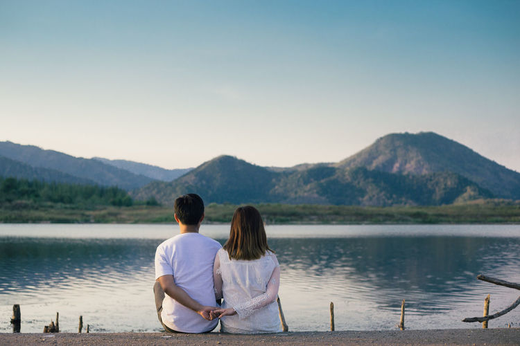 Beauty In Nature Bonding Clear Sky Couple - Relationship Day Friendship Lake Leisure Activity Lifestyles Love Men Mountain Nature Outdoors Real People Rear View Relaxation Scenics Sitting Togetherness Tranquility Two People Water Women Young Women