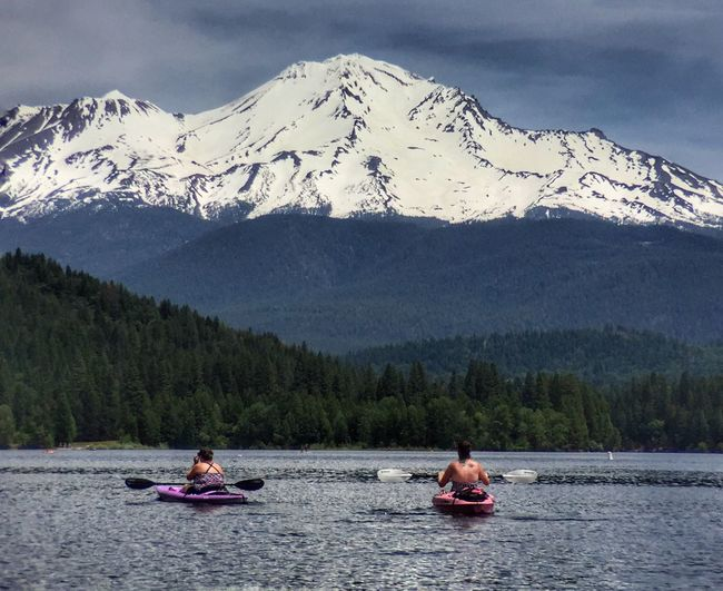 People in kayak on lake against snowcapped mountains