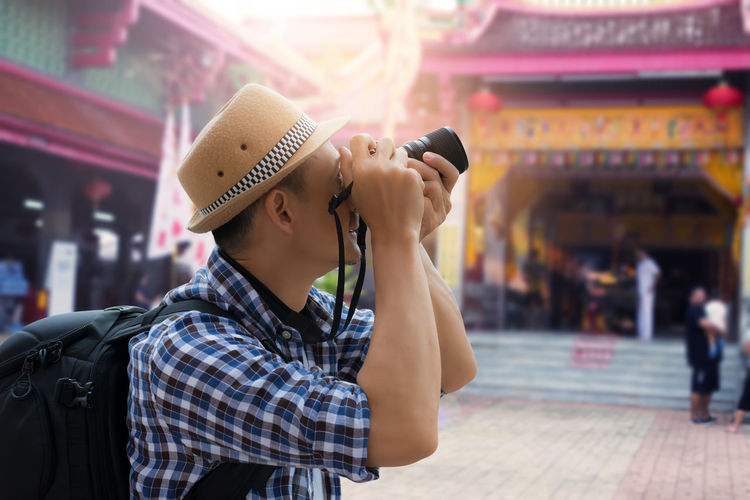 Man Photographing Temple Through Camera