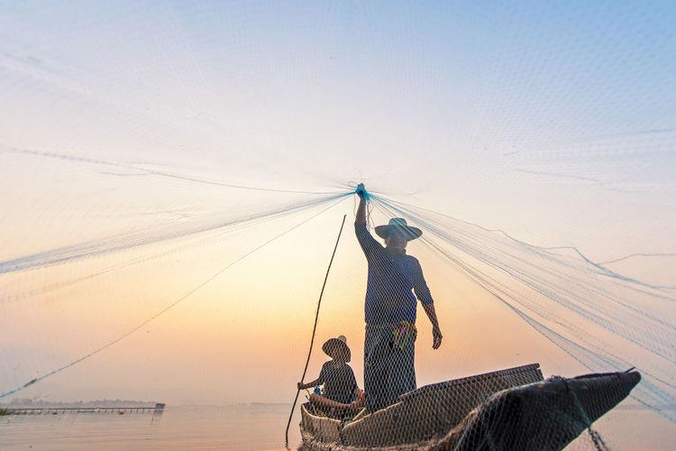 Fishing net on shore against sky during sunset