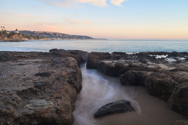 Rocky shore and sea against sky during sunset