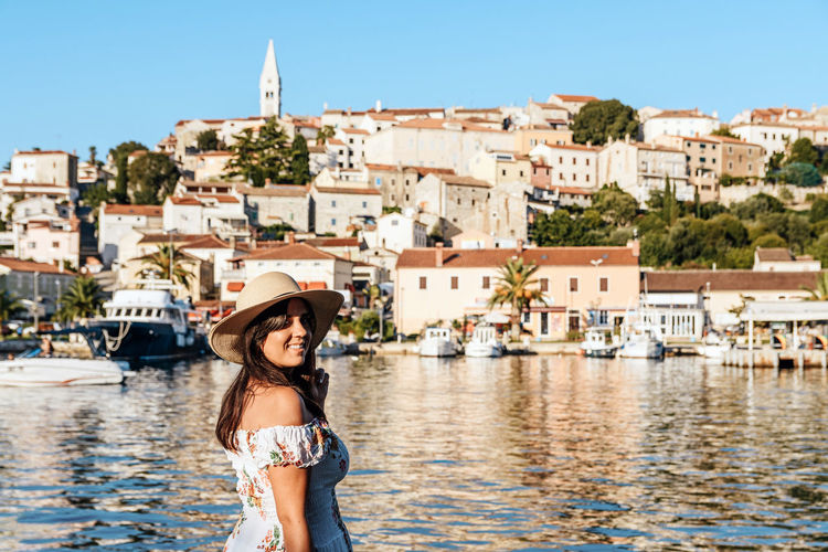 Portrait of smiling woman against buildings in city, old town by sea, summer, travel.