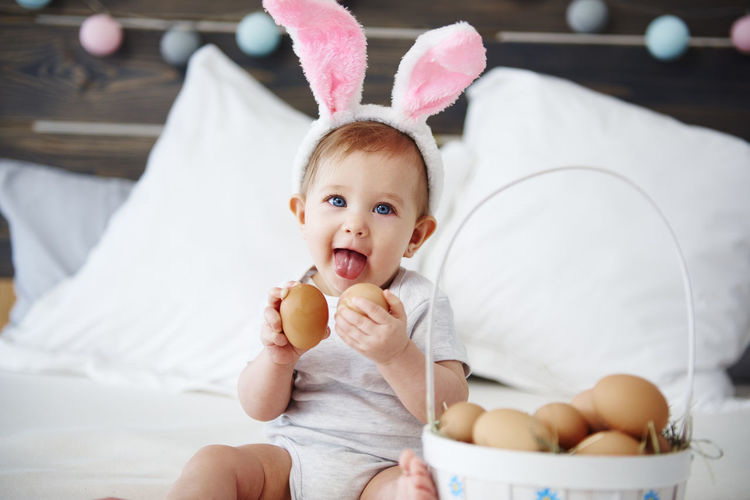 Portrait of cute baby girl with eggs sitting on bed at home