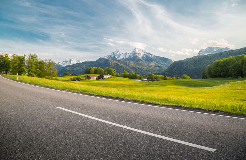 Landscape and mountains by road against sky