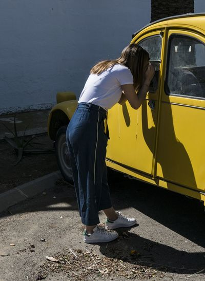 Side view of woman on car
