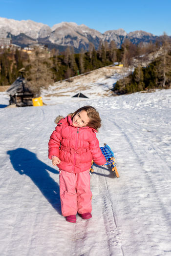 Portrait Of Girl On Snow Covered Mountain Against Sky