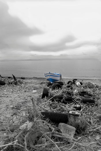 environmental pollution with a polluted beach Abandoned Beach Detritus Environmental Horizon Over Water Nature Polluted Pollution Refuse Rubbish Scenics Sea Sky Tranquil Scene Tranquility Waste Water